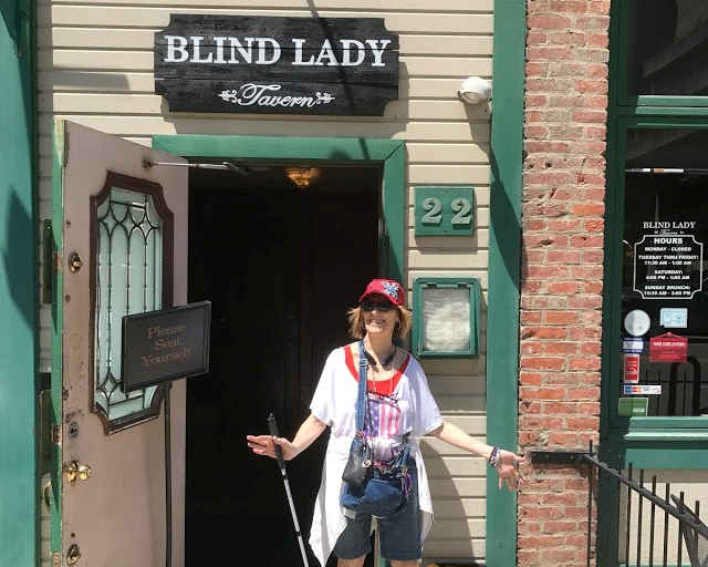 Photo of Tenacious Blind Girl. Woman in red hat sunglassesses holding white cane under the blind lady tavern in Columbus, Ohio.
